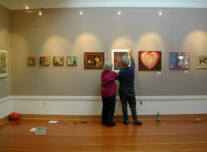 Here volunteers, Judy Sorrel and Vivi Tallman, are hanging the first show - Art About Community - at the North County Recreation District Gallery in November, 2005.